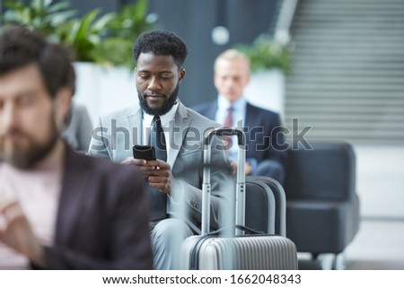 Horizontal portrait of young African-American businessman sitting in departure lounge surfing Internet on his smartphone stock photo