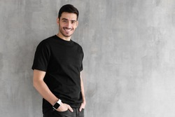 Horizontal portrait of young man standing isolated against gray textured wall feeling confident and looking optimistic in casual clothes, copyspace for advertising your goods or services