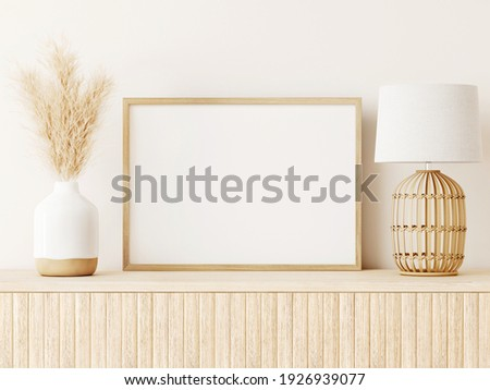 Horizontal poster art mockup with beige wooden frame, dried grass in vase, wicker basket lamp on empty warm white background. Japandi interior decoration. A4, A3 format. 3d rendering, illustration.