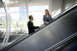Horizontal profile shot of a businessman and businesswoman smiling at each other on an escalator going up in a building.