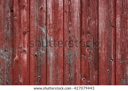 Horizontal red barn board wall from Old Barn. Textured and peeling red paint from old farm building.