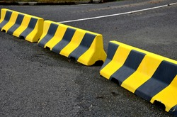 horizontal road marking lanes. highway concrete barriers on the road. vehicle collision lane separator. yellow color with black stripes. the road is not finished and ends in field concrete barriers