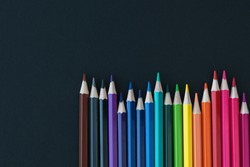 horizontal  row of multicolored pencils on dark blue background. Back to school and buying school supplies. Educational concept.