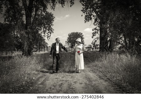 horizontal sepia vintage looking image of a happy wedding couple walking down a path holding hands and smiling at one another with grass and tall trees framing them in the background