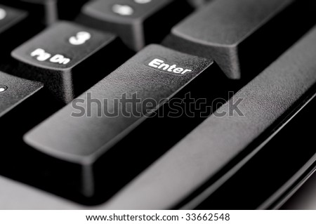 Horizontal shallow focus macro of an Enter key on a black computer keyboard