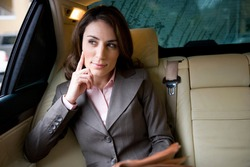 Horizontal shot of a businesswoman sitting in the backseat of a car holding financial broadsheet newspaper looking out of window and thinking.
