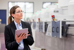 Horizontal shot of a businesswoman using a digital tablet by the machines in a manufacturing plant with copy space.
