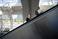 Horizontal shot of a couple of middle-aged businessmen using escalators in the airport