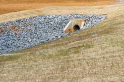 Horizontal shot of a culvert and drainage ditch under construction.   Drainage ditch pipe in background.