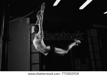 Horizontal shot of a fitness female athlete working out on gymnastic rings grip arms body care healthy confident determined motivation improvement fitness athlete women beauty concept. #775002958