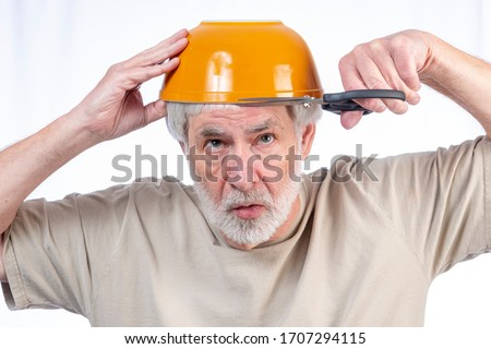 Horizontal shot of a gray haired man who's been in quarantine too long attempting to use a bowl to guide him in cutting his own hair.