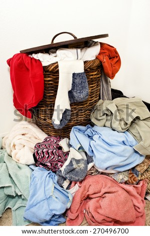 Horizontal Shot Of A Laundry Basket Spilling Out Onto The Floor With Dirty Clothes/ Time To Wash Some Dirty Laundry