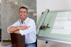 Horizontal shot of a middle-aged male architect holding a pencil and sitting in front of a drafting a board while smiling at the camera