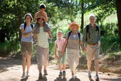 Horizontal shot of a multi-generational family with boy on the father's shoulder hiking on a mountain trail smile at the camera.