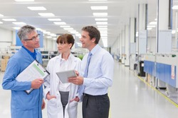Horizontal shot of a scientist, technician and a businessman under discussion on a factory floor with copy space.