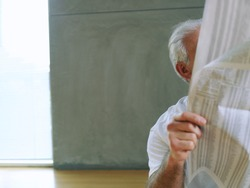 Horizontal shot of a senior man reading a newspaper with obscured face and copy space.