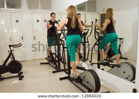 Horizontal shot of a smiling man and woman, looking at each other, using elliptical machines at the gym.