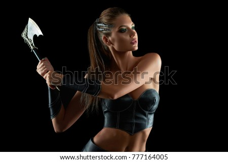 Horizontal shot of a stunning female fighter in leather traditional Amazons tribe battledress posing fiercely with an axe on black background historical culture warrior protector sexy.