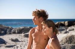 Horizontal shot of a teenage couple looking sideways standing on a rocky beach terrain on a sunny day.