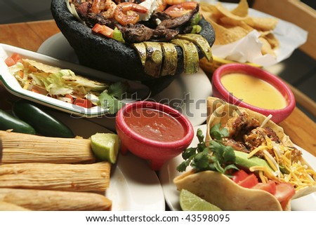 Horizontal shot of a variety of Mexican dishes. Shallow dof with central portion of image in focus.