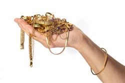 Horizontal shot of a woman's hand and arm holding a pile of gold costume jewelry and wearing a bracelet.  White background with copy space.