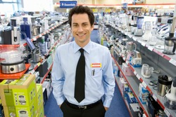 Horizontal shot of a young man standing with his hands in his pockets in the middle of the electronics aisle in the shop