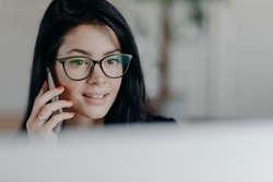 Horizontal shot of attractive brunette female employee with concentrated face expression, talks on mobile phone, has cellular conversation, wears spectacles for vision correction, busy working