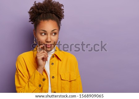 Horizontal shot of attractive curly young lady plans her vacation, keeps hand near lips, looks aside right, thinks and daydreams, dressed in yellow clothes, being deep in thoughts, models indoor