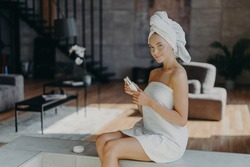 Horizontal shot of attractive lovely woman sits against cozy room background applies body lotion after taking bath uses cosmetic product for glowing skin wrapped in towel undergoes beauty treatments