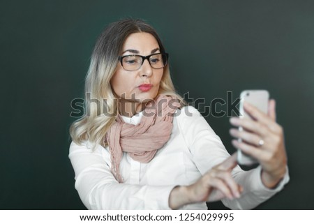 Horizontal shot of attractive middle aged lady in eyewear using modern electronic device indoors, taking selfie or browsing pictures, pouting lips. People, age, technology and communication concept