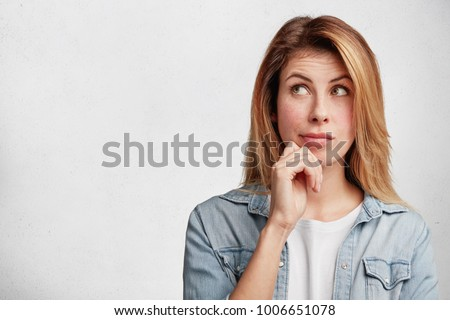 Horizontal shot of attractive young female model with pensive contemplating expression, ponders about something, dressed in casual denim shirt, isolated over white background. Facial expressions