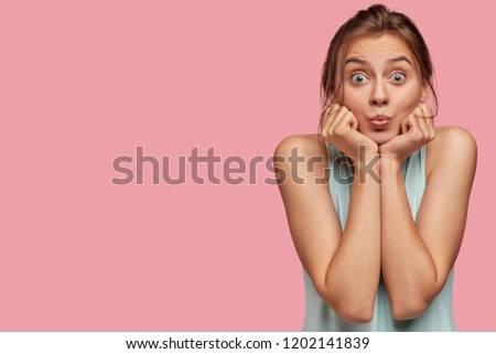 Horizontal shot of beautiful dark haired woman keeps hands under chin and purses lips for making kiss, has stunned expression and bugged eyes, poses over pink background with free space aside on left
