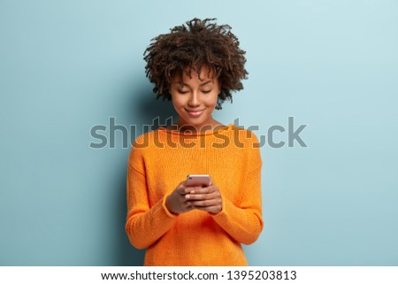 Horizontal shot of beautiful satisfied female teenager focused in smartphone device, chats online with friends, checks notification received on email, being always in touch, wears casual orange jumper