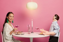 Horizontal shot of beautiful woman in festive clothing holds glass of cocktail, meets with man in restaurant for festive dinner, have date with candle, express love and affair. Romance, dating
