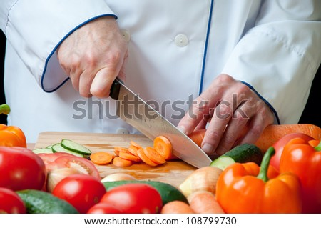 Horizontal shot of chef's hands chopping carrot
