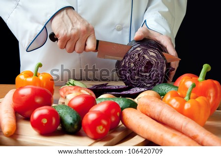 Horizontal shot of chef's hands cutting red cabbage head