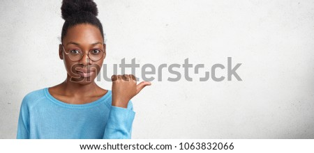 Horizontal shot of confident dark skinned beautiful African American female teacher, wears spectacles, shows something at blank copy space for your advertisment or promotional text. Look there