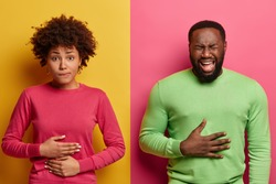 Horizontal shot of dark skinned couple touch stomachs, suffer from chronic gastritis, being hungry has displeased face expressions, isolated over yellow and pink background. Healthcare concept