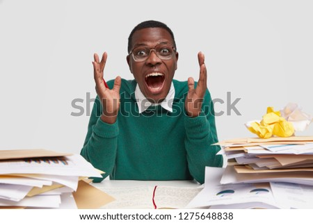 Horizontal shot of emotional financier, gestures with hands, opens mouth widely, shouts loudly shares emotions after counting profits, surrounded with papers containing financial data and graphs. #1275648838