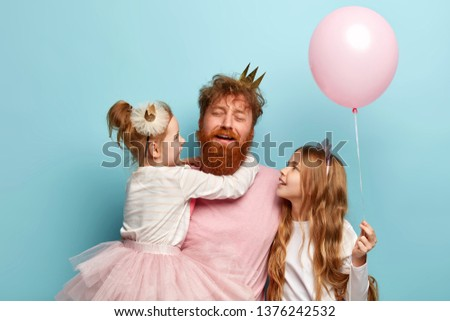 Horizontal shot of fatigue young bearded man with ginger hair, tired of playing with children. Two daughters spend holiday together with affectionate dad, hold pink balloon. Festive day concept