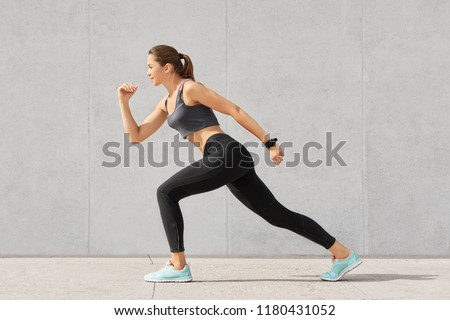 Horizontal shot of flexible woman with sporty body, stands in pose, ready to start marathon, dressed in sportsclothes, isolated over grey concrete wall. People. sport, determination concept. #1180431052