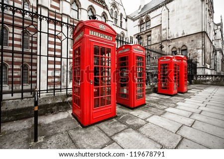 horizontal shot of four red phone boxes on London's street