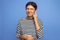 Horizontal shot of frustrated young Caucasian female with facial piercing holding finger at her ear, trying to remove wax, having painful grimace, frowning, posing isolated against blue background