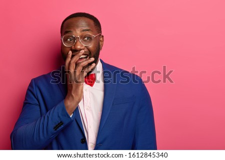Horizontal shot of funny businessman in formal wear giggles happily, covers mouth, cant stop laughing, hears funny story, keeps gaze aside, wears big optical glasses, isolated on pink studio wall