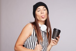 Horizontal shot of glad teenage female licks lips with tongue, holds disposable cup of aromatic coffee, takes break after analyzing piechart, wears striped blouse, listens audio book, isolated on grey