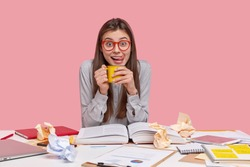 Horizontal shot of glad teenage girl licks lips with tongue, holds mug of aromatic coffee, takes break after analyzing piechart, wears spectacles and shirt, reads book, isolated on pink background