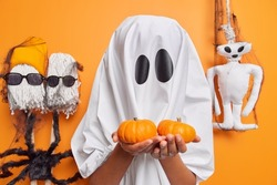Horizontal shot of halloween ghost holds two small halloween pumpkins going to carve jack o lantern wears scary costume poses against orange background with handmade creatures around. Mysterious event