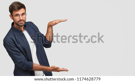 Horizontal shot of handsome Caucasian man with bristle, shows height of something with both hands, pretends holding item or thing, demonstrates size, dressed in casual outfit, isolated on white #1174628779