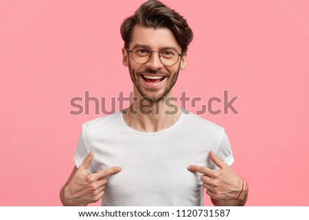 Horizontal shot of handsome cheerful hipster male indicates at white t shirt, shows blank space for your logo, being in high spirit, isolated over pink blank wall. Positive emotions and advertisement #1120731587