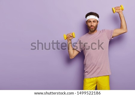 Horizontal shot of handsome unshaven man has workout in gym, trains biceps with sport instructor, wears active wear, white headband, stands against purple studio wall, copy space aside. Exercising